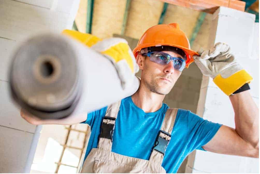 Construction worker holding his orange protective helmet.